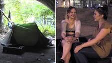 Ett tält under en bro. Cat och Shelby pratar och skrattar.