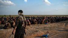 Bild på tillgångatagna män från IS sista fäste i Baghouz i östra Syrien.