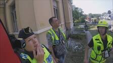 Två polisen och en brandman står på explosionsplatsen och tittar upp mot en husfasad.