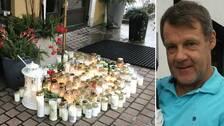 Mängder av gravljus och blommor utanför en entré samt man iklädd blå tröja