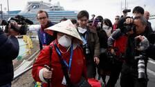 En av passagerarna som under onsdagen lämnar karantänen på fartyget Diamond Princess.