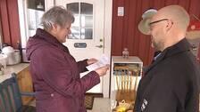 Äldre gråhårig kvinna tar emot matkassar av en yngre skäggig man med glasögon