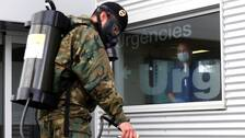 En spansk militär desinficerar utanför ett sjukhus i Barcelona.