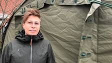 Kvinna står framför ett grönt corona-tält.