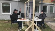 En man med keps och en man i rullstol sitter på varsin sida av ett plexiglas.