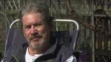 Rolf Andersson sitter på en stol utomhus med grenar i bakgrunden.