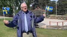Peter Friström, ordförande i kommunfullmäktige (S) står framför scenen på Torekällberget och viftar med Sverige-flaggor
