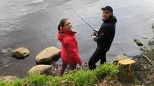 Kvinna och man står vid sjö och fiskar