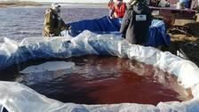 Hjälparbetare arbetar med att rena ambarnajafloden från oleutsläppet.