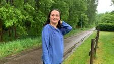 En kvinna i blå skjorta står vid en lantväg/gångväg intill en skog, ett staket är på ena sidan. Hon tittar uppåt, mot fåglarna.