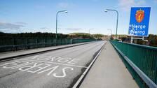 """En asfalterad väg med orden Sverige och Norge skrivet i vit färg. Vid sidan om en blå skylt med texten """"Norge"""" i vitt."""