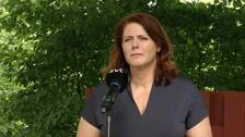 Ebba Östling (S), kommunstyrelsens ordförande i Botkyrka, står framför en mikrofon, framför ett rött staket och en buske.