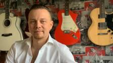 Man i vit skjorta sitter framför vägg där det hänger tre gitarrer.
