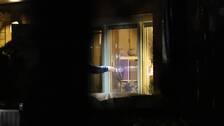En tekniker pekar mot ett fönster med sex kraftiga kulhål.