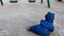 Ett barn i overall leker intill gungor.