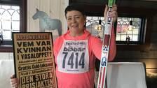 medelålders kvinna som håller upp löpsida från aftonbladet och ett par skidor