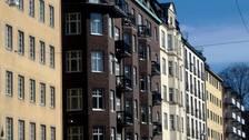 Lägenhetsfasader i beige, grått och vitt.