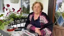 En äldre dam sitter på sin altan med en tidning framför sig efter att hon fått komma tillbaka sitt hem.