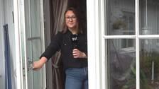Kvinnlig reporter står i en dörröppningen med en mikrofon i handen.