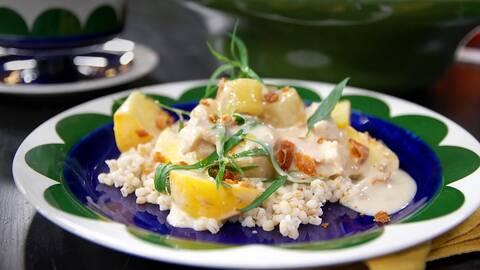 Vit tallrik med maträtt bestående av potatis, matvete, vit sås och gröna kryddblad på.
