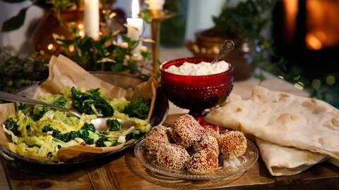 Bollar med rödbetsfalafel på glasfat. Bredvid står röd skål med äppelyoughurt och ett fat med stekt kål, samt libanesiskt bröd.