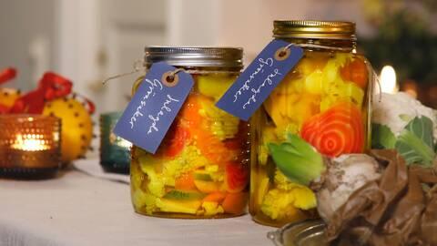 Glasburkar med inlagda grönsaker i. Burkarna är dekorerade med namnlappar.