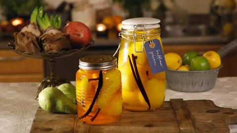 Inlagda päron i två glasburkar. Burkarna är dekorerade med namnlapp. I bakgrunden syns fruktskålar.