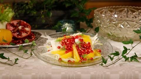 Fänkålssallad serverad på glasfat, dekorerad med fänkålsdill och granatäpplekärnor.
