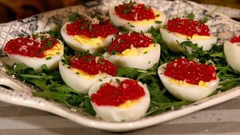 Ägghalvor ligger på en bädd av ruccola. Äggen är dekorerade med hallonröd rom och gräslök.