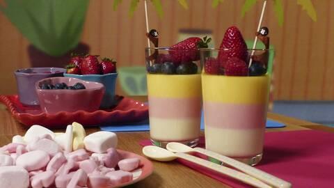Ett fat med godis, ett fat med skålar med blåbär, jordgubbar och hallon, och två glas randig godispannacotta toppad med blåbär, jordgubbar, hallon och två små parasoll.