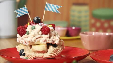 Ett fat med marängtårta, toppad med hallon och två flaggor som dekoration.