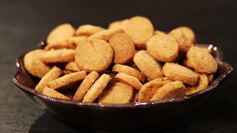 Bruna små kakor i en brun skål.