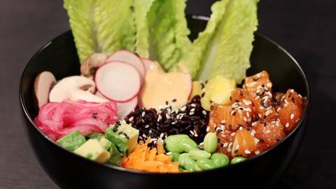 Svart skål med tre gröna salladsblad, skivade rädisor, laxbitar, sojabönor, avocado, svamp och rödlök.