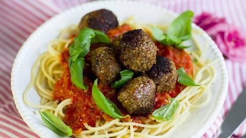 Solrosbollar på en tomatsåsbädd, ljus pasta och gröna kryddblad.