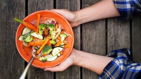 Grönsaker i buljong i en orange skål.