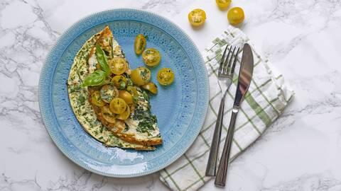 En omelett på en blå tallrik. Gula körsbärstomater ligger runt om. Ett par bestick på en grön och vitrandig handduk.