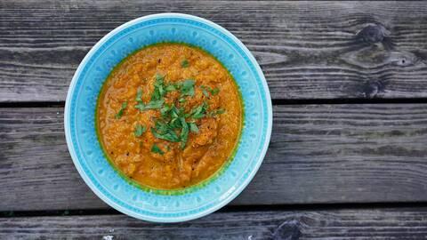 Morotssoppa i en blå tallrik med gröna färska kryddor på.