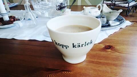 En kaffekopp med kaffedryck i en vit kopp på ett träbord.