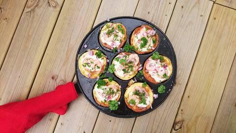 Ett plättlägg med sju små plättar med räkor och persilja.