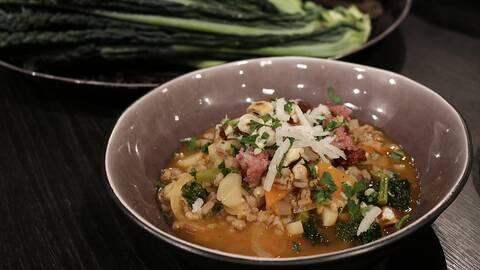 Toscansk dinkelsoppa med kål och grönsaker, serverad i en skål.