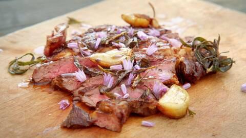 En träbricka med en saftig bit grillad biff, med rosmarin och vitlök, dekorerad med lila blommor.