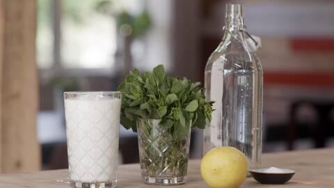 På ett bord står ett glas ayran (turkisk drickyoghurt), ett glas med mynta, en citron, salt i en liten skål och vatten.