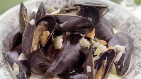En tallrik med kryddade blå musslor.