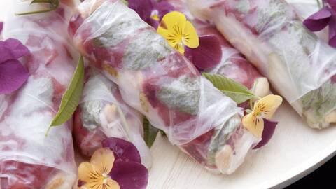 En träbricka med rullar gjorda med rispapper, fyllda med grönsaker och dekorerade med gula och lila blommor.