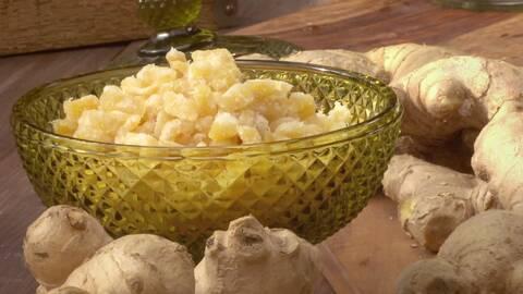 En glasskål med kanderad ingefära i bitar. Runt om det finns naturliga ingefära.