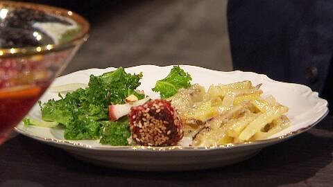 En tallrik med vegansk julmat: äppelsallad, rödbetorsbullar och vegansk jansson.