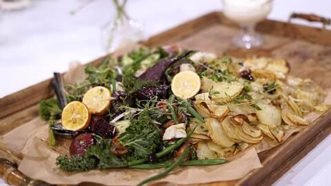 En träbricka med rostad potatis Provencale, med citronbakade rödbetor och sallad.