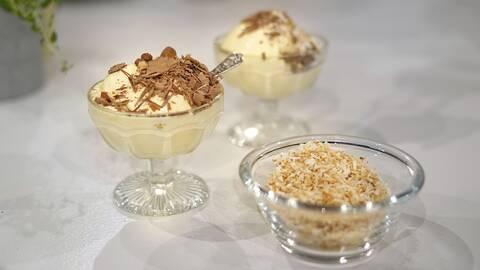 Två skålar med mangoglass, toppade med riven choklad, och en skål med riven kokos.