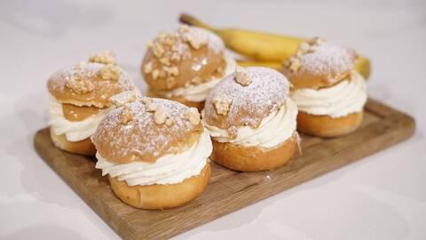 En träbricka med fem banoffee-semlor, fylda med dulce de leche och banan. Recept av Gustaf Mabrouk.