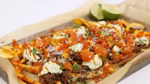 En ugnsbricka med sötpotatis i strimlor, lagad med tacotillbehör: lök, paprika, tomat, guacamole, sås och lime.